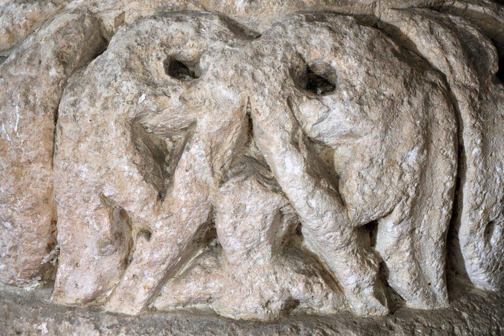 Vézelay - Abbatiale - piédroits de droite du tympan central de la nef - base de colonne : un buste d'enfant inséré dans un triangle équilatéral formé par les trompes d'éléphants affrontés qui peuvent aussi, vus de face, évoquer un oiseau de nuit (v. 1130)