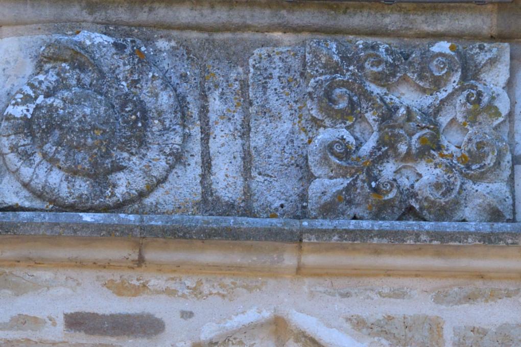 Saint-Père-sous-Vézelay - Médaillons du troisième étage du clocher : l'ammonite fossile et la croix fleurdelisée (XIIIe s.)